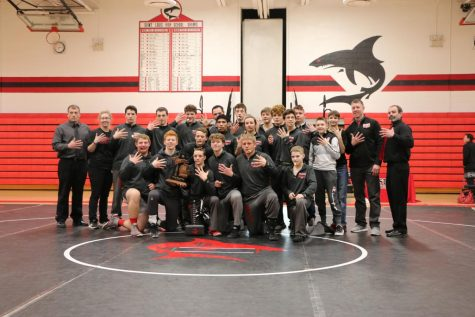 Wrestling team picture holding the district trophy
